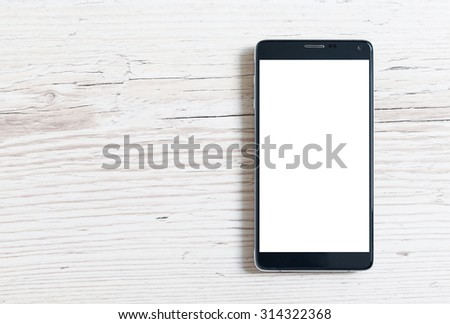 Black smart phone with isolated screen on wooden table - stock photo