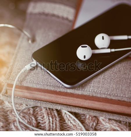 black smartphone and white headphone on beige note pad.