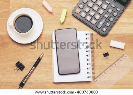 Black smartphone on wooden table with calculator and other office tools. Mock up