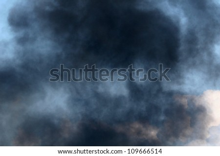 Black Smoke from a Gasoline and Dynamite Explosion (smoke texture with blue sky contrast) - stock photo