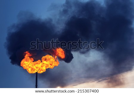 Black smoke from burning of associated gas - stock photo