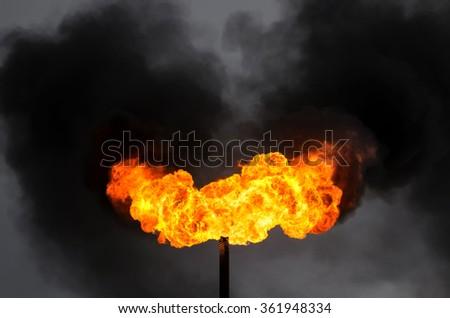 Black smoke from burning of associated gas - stock photo