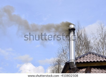 Black smoke from the chimney of a house.