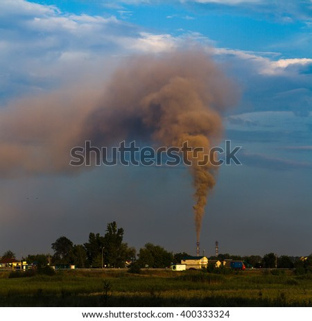 Black smoke is formed from thermal power plants. Fumes dissipate across the sky and turns to smog. A photo on the theme of global warming and environmental pollution. - stock photo
