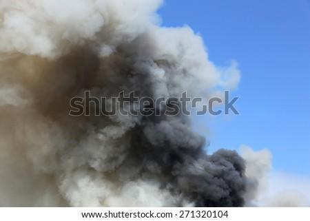 black smoke on a sky blue  - stock photo