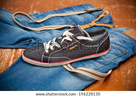 Black Sneakers and jeans with suspenders - stock photo