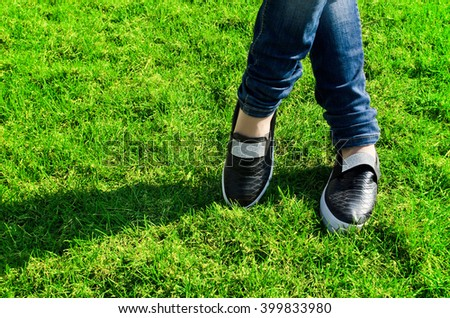 black sneakers on girl legs on grass, slip on shoes, decorated with sequins.