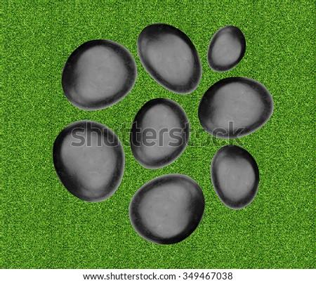 Black spa stones over green grass - stock photo