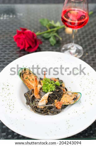 Black spaghetti with seafood and red wine - stock photo