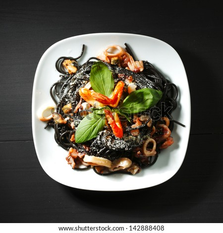 Black spaghetti with seafood on black table - stock photo