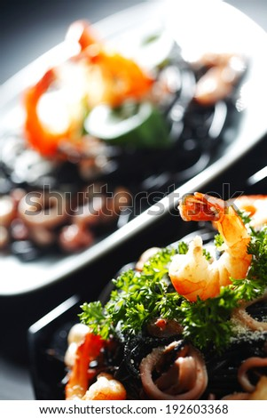 Black spaghetti with seafood on black table