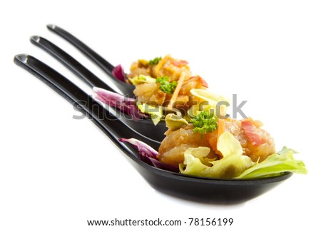 Black spoons filled with nice food isolated over white