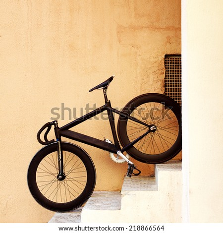 Black sport professional high speed fixed gear trek bicycle leaning on yellow urban style wall standing on stairs super bike  - stock photo