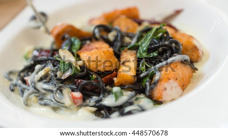 Black squid ink pasta with fried salmon and white cream sauce in white plate