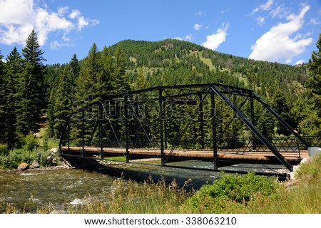 "Black steel bridge spans the Gallatin River in Montana.  Sign on bridge calls it the ""Gallatin Golden Gate.""  Gallatin Range of the Rocky Mountains rises behind it. - stock photo"