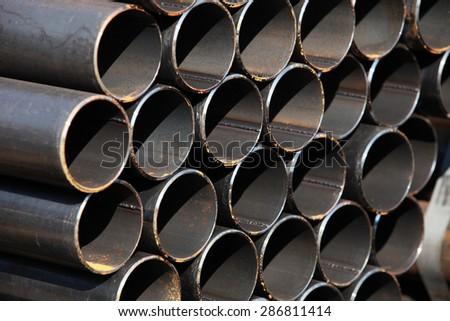 Black steel pipe bundle in industrial stockyard.  - stock photo