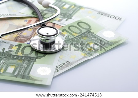 Black stethoscope close-up on top of euro banknotes side view