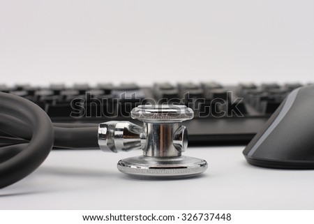 Black stethoscope ,pc mouse, keyboard  on white background, medical concept