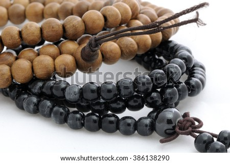Black stone and sandalwood Chinese Buddhist prayer beads isolated on a white background.