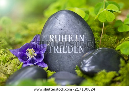 """Black stone with the Words - """"rest in peace"""" in german language - """"Ruhe in Frieden"""" - stock photo"""