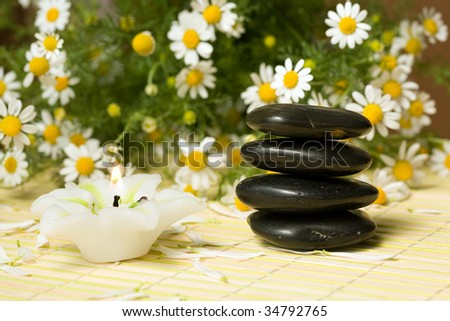 Black stones for spa massage and candle