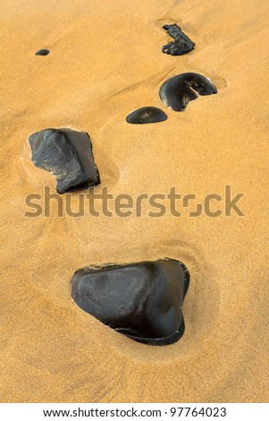 Black stones in sand background