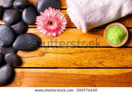 Black stones with water drops in the top left corner, flower, towel and bath salts on wooden slats. Sauna and massage concept. Horizontal composition. Top view - stock photo