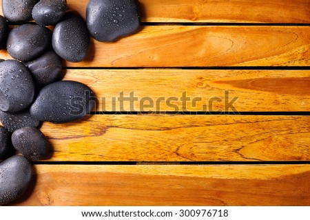 Black stones with water drops in the top left corner on wooden slats. Sauna and massage concept. Horizontal composition. Top view - stock photo