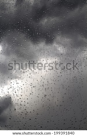 Black stormy sky and rain drops on a window, background - stock photo