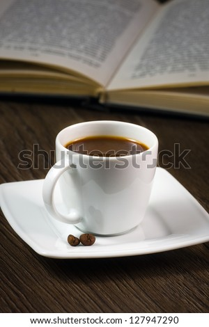 black strong coffee on the table and reading book