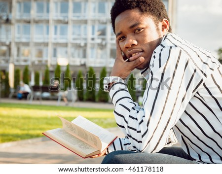 Black student in the park. Beautiful background.