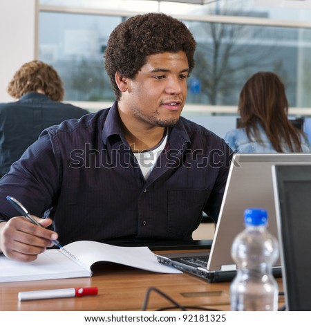 Black student working in a library, taking notes, and doing research online on his laptop, with two other students in the background - stock photo