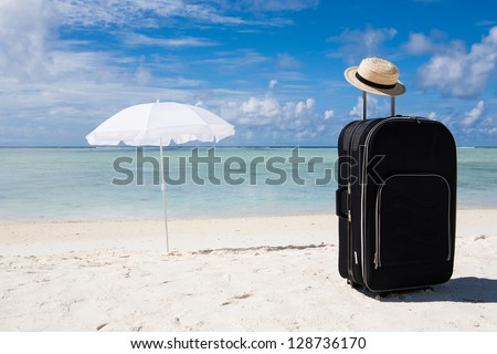 black suitcase, sun hat and white sunshade at the beach - stock photo