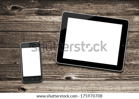 Black tablet computer ipade style and smart phone with isolated screens on old wooden desk. - stock photo