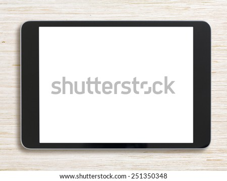 Black tablet pc or ipad on bleached wood background - stock photo