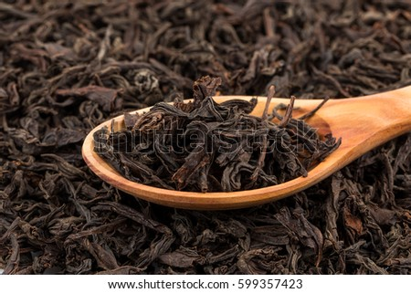 Black tea in a spoon on a black tea background. Close-up shot