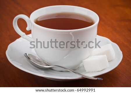 Black tea in cup with saucer on the table - stock photo