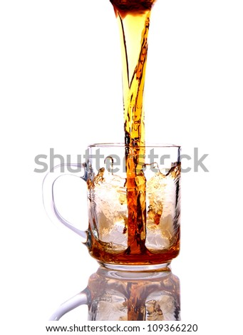 Black tea is poured into a glass cup - stock photo