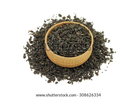 black tea leaves in a wooden bowl on a white background - stock photo