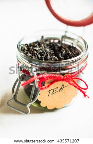 Black tea leaves in the jar with note on rustic background