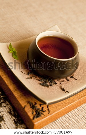 Black tea still life in a beautiful ceramic pot with mit and dry tea leaves. - stock photo
