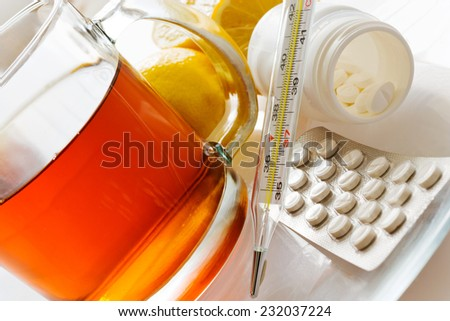 black tea with fresh lemons and flu pills in blister with thermometer - home grippe remedy - stock photo