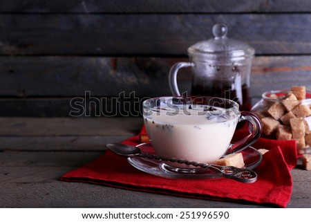 Black tea with milk and lump sugar in glassware on color wooden planks background - stock photo