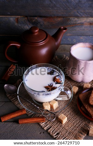 Black tea with milk in cups and teapot with lump sugar on color wooden planks background - stock photo