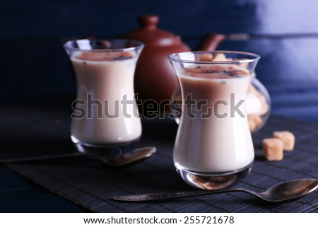 Black tea with milk in glasses and teapot with lump sugar on bamboo mat and color wooden planks background - stock photo