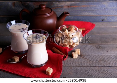 Black tea with milk in glasses and teapot with lump sugar on color wooden planks background - stock photo