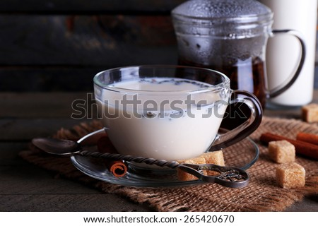 Black tea with milk in glassware and lump sugar on color wooden planks background - stock photo