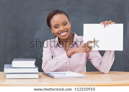 Black teacher holding a blank paper while smiling in a classroom - stock photo
