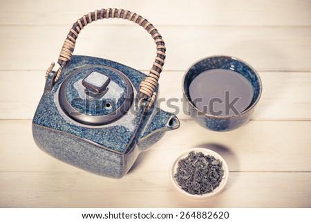 Black teapot, bowl of green tea on white wooden table - stock photo