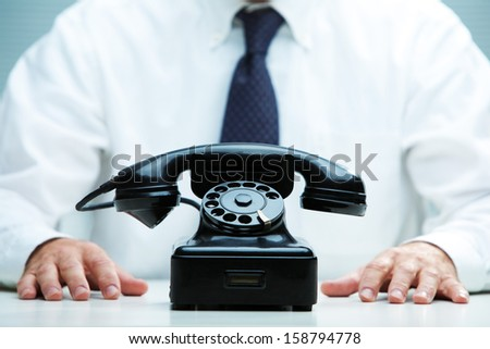 black telephone on focus with a business waiting for a call on the background - stock photo